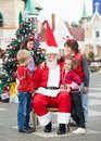 Happy children with santa claus against christmas tree in courtyard Stock Photo