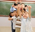 Happy children at school classroom Stock Photos