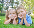 Happy children smiling in green grass two are and laying down on a yard outside with the sun shining for a summer or spring Royalty Free Stock Image