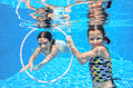 Happy children swim in pool underwater girls swimming playing and having fun kids water sport Royalty Free Stock Images