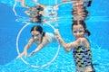 Happy children swim in pool underwater, girls swimming Royalty Free Stock Photo