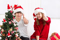 Happy children under christmas tree cheerful the with thumbs up Stock Photo