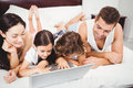 Happy children using laptop with parents on bed at home Royalty Free Stock Photo
