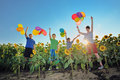 Happy childrens jumping on meadow with balloons children colorful in a field of sunflowers Stock Images