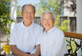 Happy Chinese Elderly Couple Sitting in Back Yard Royalty Free Stock Photo