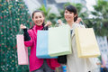 Happy chinese women go shopping with bags in business street Royalty Free Stock Image