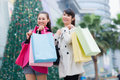 Happy chinese women go shopping with bags in business street Stock Photos