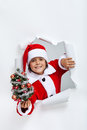Happy christmas boy giving you a small decorated fir tree leaning through hole in paper layer Stock Photography