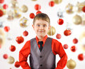 Happy christmas boy with ornament background a little child is posing against a white red and gold bulbs the is smiling and Stock Photo