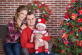 Happy Christmas Family portrait. Smiling Parents with baby daughter at Home Celebrating New Year. Christmas Tree