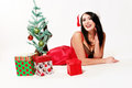 Happy christmas girl pretty woman with santa hat on and a red negligee sitting by a small tree surrounded by gifts Royalty Free Stock Photos