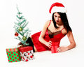 Happy christmas girl pretty woman with santa hat on and a red negligee sitting by a small tree surrounded by gifts Royalty Free Stock Photo