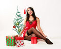 Happy christmas girl pretty woman with santa hat on and a red negligee sitting by a small tree surrounded by gifts Stock Photo