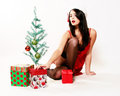Happy christmas girl pretty woman with santa hat on and a red negligee sitting by a small tree surrounded by gifts Royalty Free Stock Image