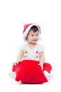 Happy christmas girl sitting and smiling little holding pillow in santa hat on white background Royalty Free Stock Photography