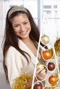 Happy christmas portrait of beautiful woman putting up decoration smiling at camera Stock Image