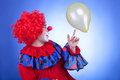 Happy clown playing with yellow ballon on blue background studio professional lighting Royalty Free Stock Photo