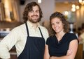 Happy coffee shop owners portrait of male and female standing together in Royalty Free Stock Photo