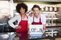 Happy colleagues posing with open sign at the bakery Stock Photos