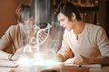 Happy college students analysing dna on digital interface in university library Stock Photos
