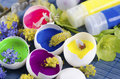 Happy colorful Easter decoration with egg shells filled with paints and spring flowers Royalty Free Stock Photo