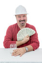 Happy construction worker holding on to tax money wearing a hard hat dollar notes destined taxes Stock Image