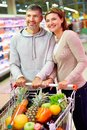 Happy consumers image of couple with cart choosing products in supermarket Stock Image