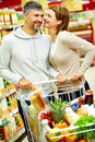 Happy consumers image of couple with cart flirting in supermarket Royalty Free Stock Photography