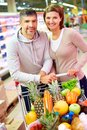 Happy consumers image of couple with cart full of products looking at camera in supermarket Stock Images