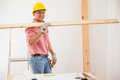 Happy contractor at work attractive latin carrying some wood while wearing protective equipment Royalty Free Stock Image