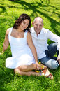 Happy couple american venenuelan sitting in the grass enjoying a day outside Royalty Free Stock Images
