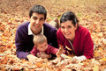 Happy couple with baby at the park in autumn family lying fallen leaves Royalty Free Stock Images