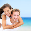 Happy couple on beach fun summer vacation multiracial young newlywed couple piggybacking smiling joyful elated in happiness Stock Image
