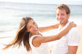 Happy couple on beach in love having fun holding around each other hugging looking at camera lifestyle portrait of healthy young Royalty Free Stock Photos