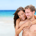 Happy couple on beach in love having fun together travel vacation holidays tropical beautiful interracial asian Stock Image