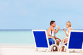 Happy couple on beach relaxing in chairs and drinking champagne Stock Images
