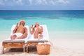 Happy couple on beach resort tanning sunbed and eating tasty sweet ice cream enjoying summer time beautiful sandy coast Stock Photo