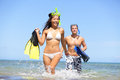 Happy couple beach summer vacation travel fun woman and men laughing with joy with snorkeling fins equipment on tropical Royalty Free Stock Photo