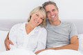 Happy couple in bed smiling at camera Royalty Free Stock Photos