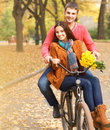 Happy couple on bicycle walking in autumn park young with Stock Image
