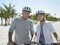 Happy couple with bicycles on tropical beach portrait of senior Royalty Free Stock Photos