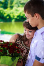 Happy couple with a bouquet of red roses hugs in a summer park Stock Images
