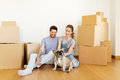 Happy couple with boxes and dog moving to new home Royalty Free Stock Photo