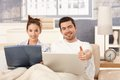 Happy couple browsing internet in bed at home Royalty Free Stock Photography