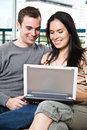Happy couple browsing internet at home Stock Image