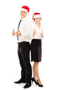 Happy couple of business persons in christmas hats young posing and holding thumbs up image isolated on white Royalty Free Stock Images