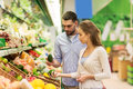 Happy couple buying avocado at grocery store Royalty Free Stock Photo