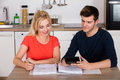 Happy Couple Calculating Invoice In Kitchen Royalty Free Stock Photo