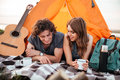 Happy couple camping on the beach laying in the tent Royalty Free Stock Photo