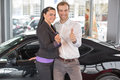 Happy couple with car key in dealership after buying an automobile a Royalty Free Stock Photo